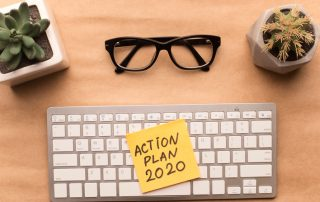 Desk top with keyboard and glasses, post-it on keyboard that says Action Plan 2020