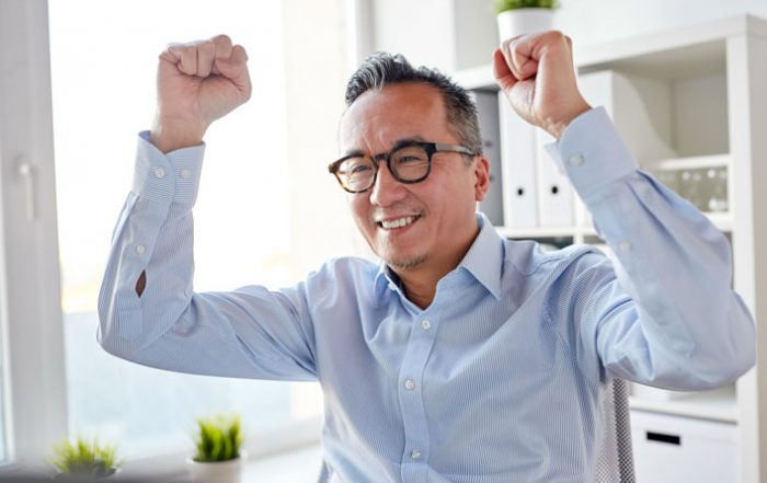 Man sitting at desk smiling with arms raised in celebration