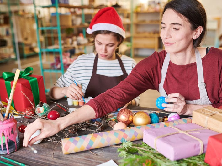 Two women at work with wrapping paper and holiday ornaments.