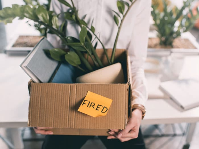 Business person holding box of belongings after being terminated from job