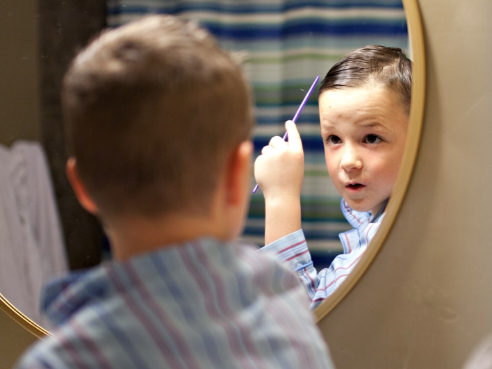 Young boy combing his hair and looking at himself in the mirror